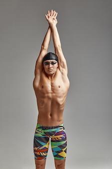 Pływak w kąpielówkach szykuje się do startu, atleta na szarym tle przygotowuje się do pływania, ja pozuję do pływania w basenie w okularach i masce.