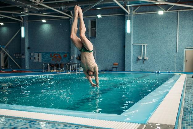 Pływak w okularach skaczący z wieży do wody, trening na basenie, zdrowa aktywność fizyczna. sporty podwodne