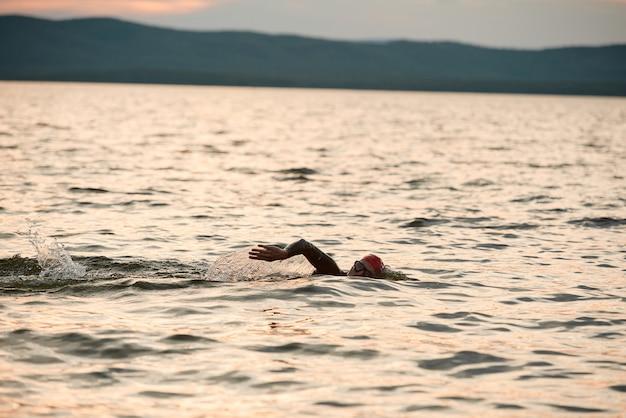 Pływak w stroju kąpielowym pływa samotnie w jeziorze podczas zachodu słońca na łonie natury