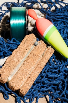 Pływak wędkarski i żyłka na pokładzie korkowym nad niebieską siecią rybacką