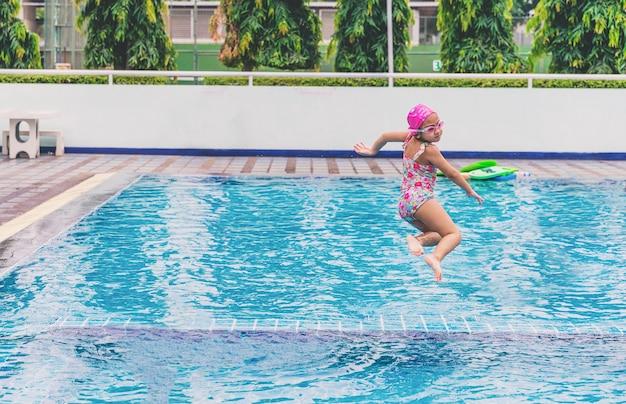 Pływanie, mała dziewczynka zabawy skakanie do basenu