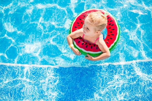 Pływanie, wakacje - urocza uśmiechnięta dziewczyna bawiąca się w niebieskiej wodzie z kołem ratunkowym i arbuzem.