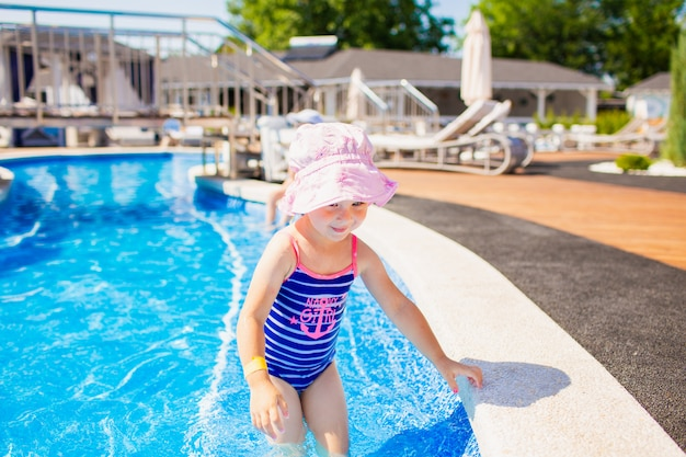 Pływanie, wakacje - urocza uśmiechnięta dziewczyna w różowym kapeluszu i niebieskim stroju kąpielowym bawi się w niebieskiej wodzie w basenie.