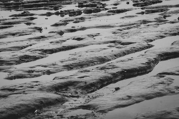 Pływowy mudflat. falująca plaża. odpływ natura na wybrzeżu. szare tło dla smutnego życia w złym dniu koncepcji. wieczorem plaża morska. zjawisko pływów na brzegu morza.