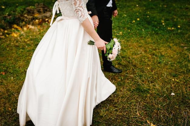 Po ceremonii ślubnej panna młoda i pan młody idą na zieloną trawę