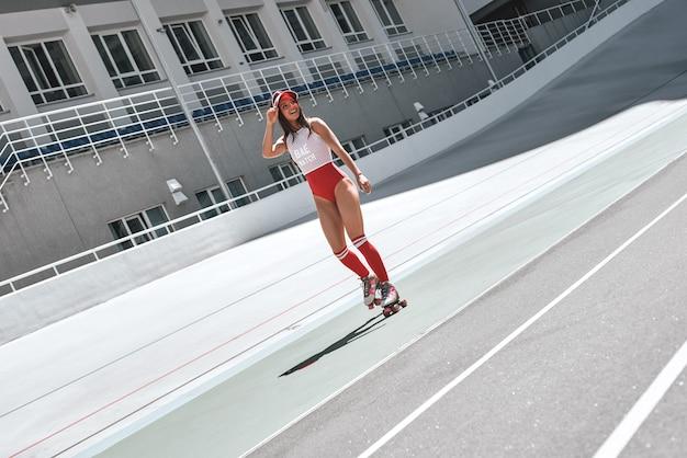 Po co chodzić, kiedy można jeździć na łyżwach piękna kobieta jeździ na rolkach w skateparku uśmiechnięta i