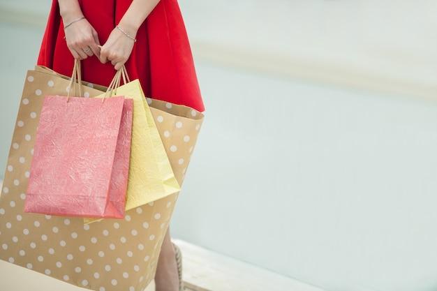 Po dniu zakupów. zakończenie młodej kobiety przewożenia torba na zakupy podczas gdy chodzący wzdłuż ulicy