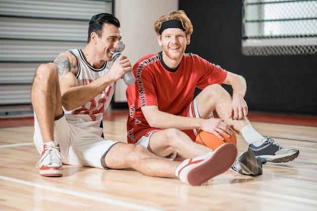 Po grze. dwóch młodych mężczyzn odpoczywa po meczu koszykówki i rozmawia