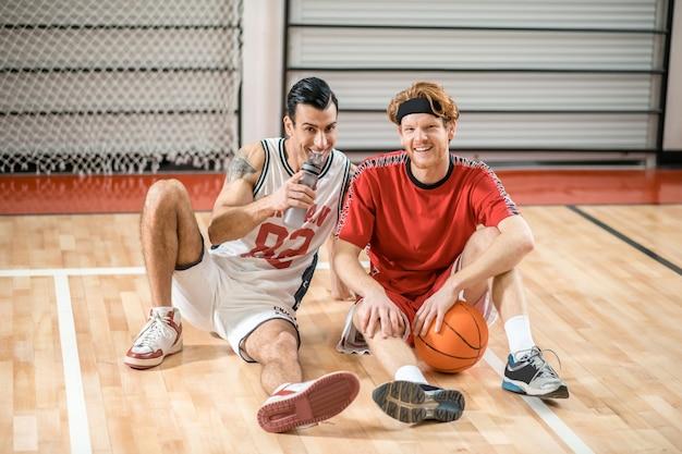 Po grze. dwóch przyjaciół siedzi na podłodze w siłowni i odpoczywa po meczu