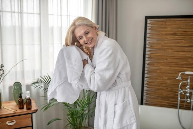 Po kąpieli. uśmiechnięta blondynka susząca włosy ręcznikiem po kąpieli