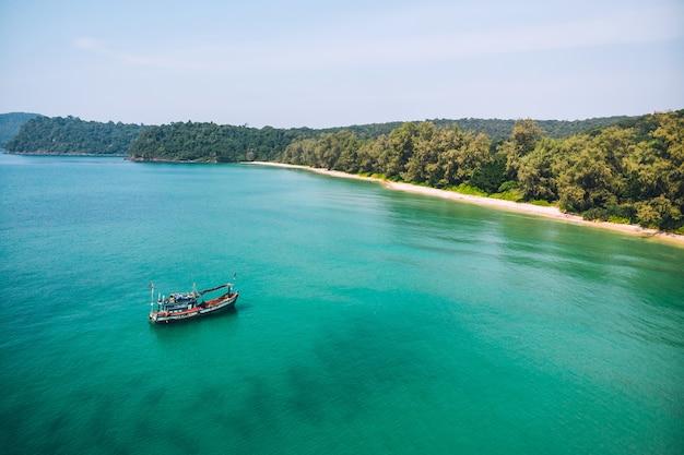 Po morzu pływają łodzie rybackie, które łowią ryby. łódź rybacka to łódź zbudowana z drewna i mała łódź rybacka. w tle widać wyspę i błękitne morze.