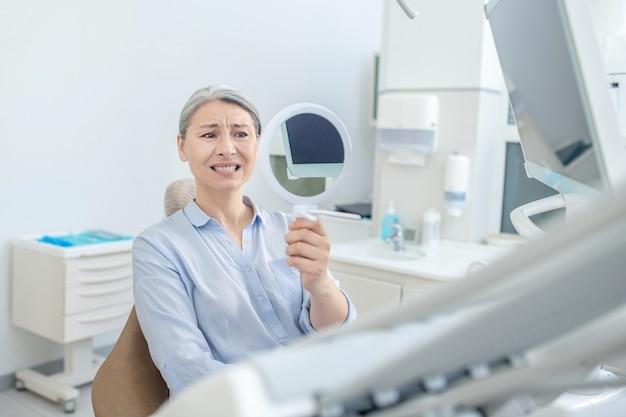 Po odbudowie zębów. kobieta siedzi w gabinecie dentystycznym z lustrem w rękach