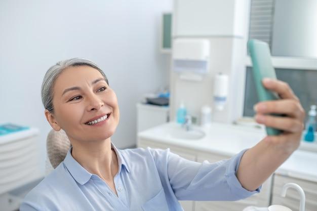 Po odbudowie zębów. uśmiechnięta ładna dojrzała kobieta ze smartfonem w gabinecie dentystycznym