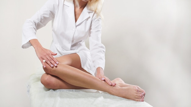 Po profesjonalnym depilacji stóp w salonie piękności kobieta dotyka gładkich nóg
