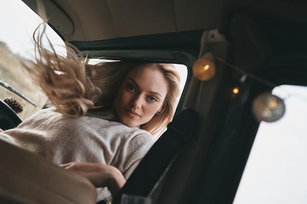 Po prostu beztroski. atrakcyjna młoda uśmiechnięta kobieta wychylająca się przez okno furgonetki i patrząca w kamerę podczas podróży samochodem