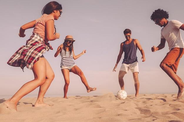 Po prostu dobrze się bawię. grupa wesołych młodych ludzi bawiących się piłką nożną na plaży z morzem w tle