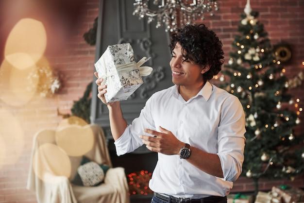 Po prostu dobrze się bawię z zapakowanym prezentem. młody człowiek stojący w pięknym urządzonym pokoju i trzymając białe pudełko na prezent w nowym roku