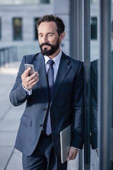 Po prostu go użyj. przyjemny biznesmen cconfident za pomocą swojego smartfona, trzymając laptopa