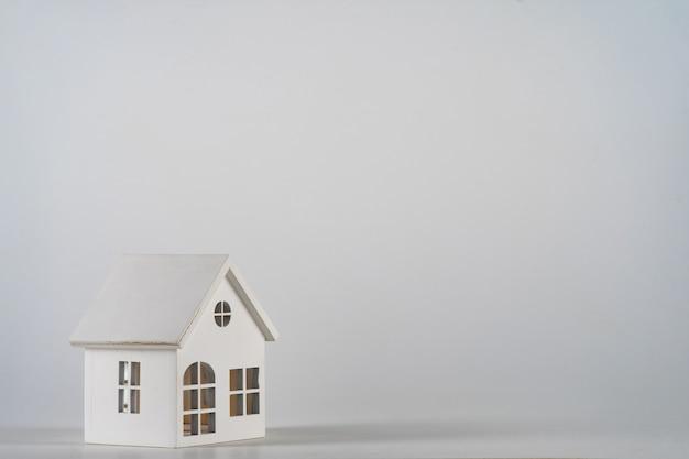 Po prostu minimalistyczny design z miniaturowym domkiem z zabawkami na białym tle. koncepcja wymarzonego domu hipotecznego