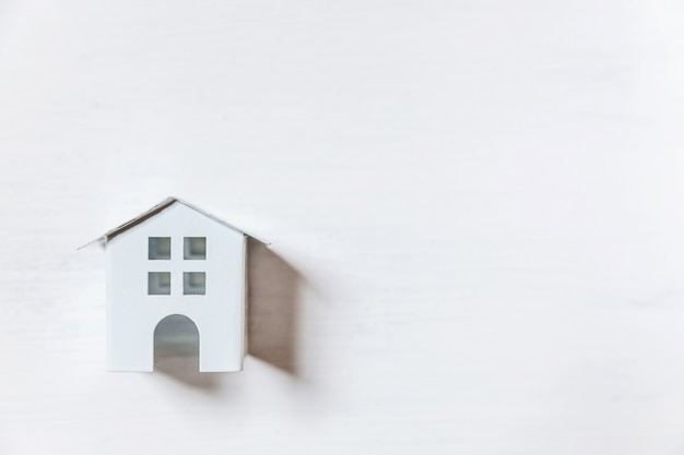 Po prostu minimalistyczny design z miniaturowym domkiem z zabawkami na białym tle