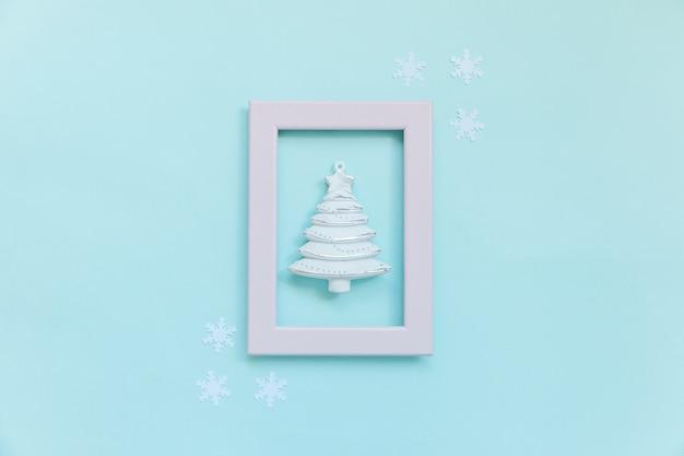 Po prostu minimalna kompozycja obiektów zimowych jodły w różowej ramce na białym tle na niebieskim tle