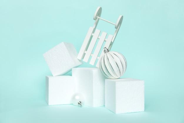 Po prostu minimalna kompozycja obiektów zimowych ornament i podium kostki na białym tle pastelowe niebieskie tło