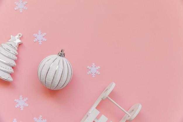 Po prostu minimalna kompozycja obiektów zimowych ozdoba piłka sanie jodłowe izolowane na różowym pastelowym modnym tle