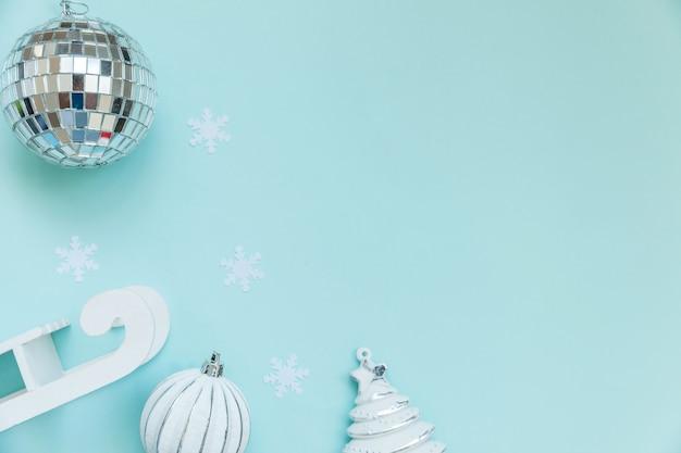 Po prostu minimalna kompozycja obiektów zimowych ozdoba sanki jodła piłka na niebieskim pastelowym modnym tle