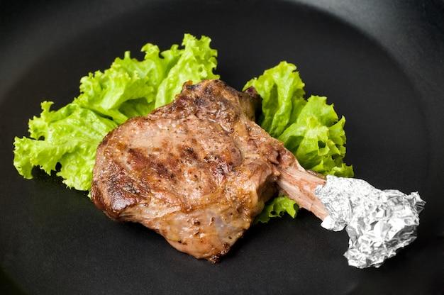 Po prostu pieczony soczysty stek ribeye leżący na czarnej płycie lub patelni z powłoką zapobiegającą poparzeniu