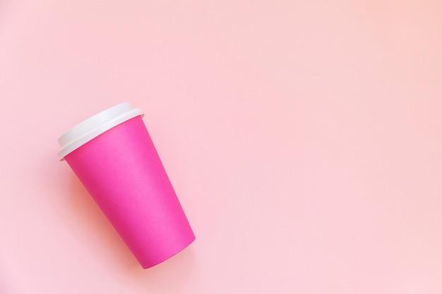 Po prostu płaska filiżanka kawy z różowego papieru na różowym stole