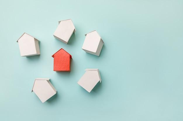 Po prostu płaska konstrukcja z miniaturowym czerwonym domkiem z zabawkami wśród białych domów na pastelowych b...