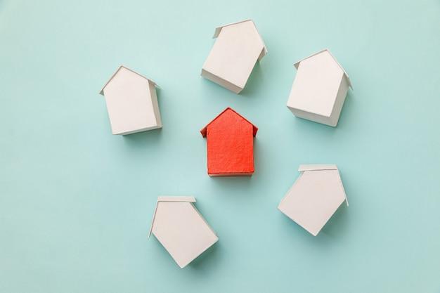 Po prostu płaska konstrukcja z miniaturowym czerwonym zabawkowym modelem domu wśród białych domów na pastelowych b...