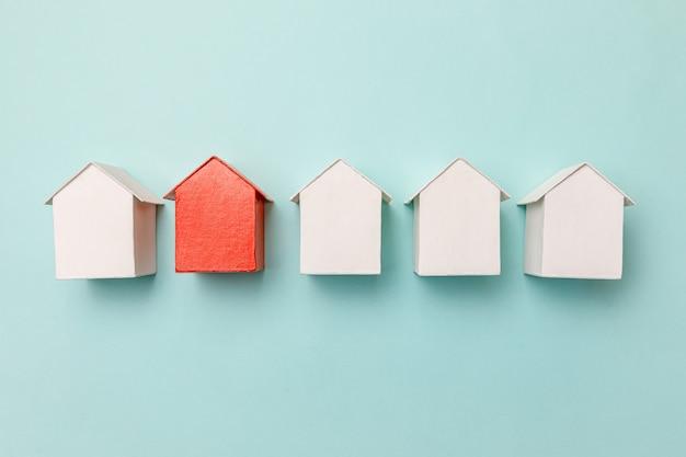 Po prostu płaska konstrukcja z miniaturowym czerwonym zabawkowym modelem domu wśród białych domów na pastelowym niebieskim tle. branża nieruchomości. unikalna koncepcja wyboru sąsiedztwa dla społeczności.
