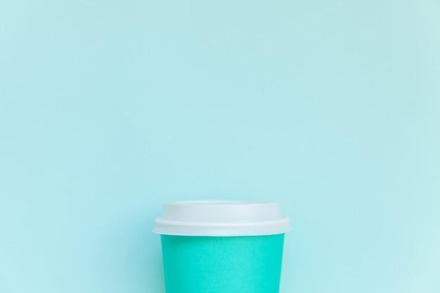 Po prostu płasko leżał projekt niebieski papierowy kubek do kawy na niebieskim tle pastelowych