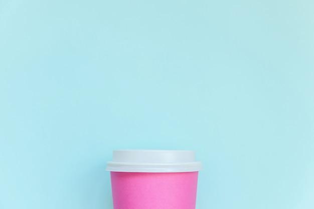 Po prostu płasko połóż różowy papierowy kubek do kawy na niebieskim pastelowym tle