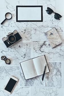 Po prostu podróżuj. ujęcie pod dużym kątem okularów przeciwsłonecznych, aparatu fotograficznego, kompasu, lupy, pamiętnika
