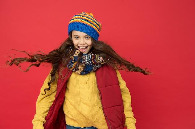 Po prostu puściłem włosy. szczęśliwe dziecko z długimi włosami. mała dziewczynka nosi ciepłą czapkę na głowie. salon fryzjerski i kosmetyczny. salon fryzjerski. zimowa pielęgnacja włosów. codzienna pielęgnacja włosów w niskich temperaturach.
