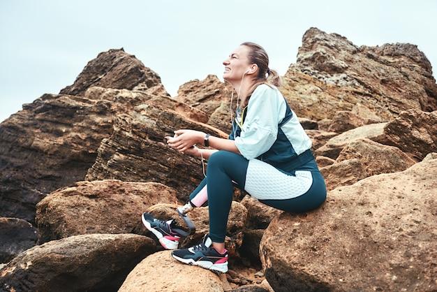 Po prostu szczęśliwe uśmiechnięte niepełnosprawne kobiety w sporcie noszą protezę nogi siedzącą na głazach