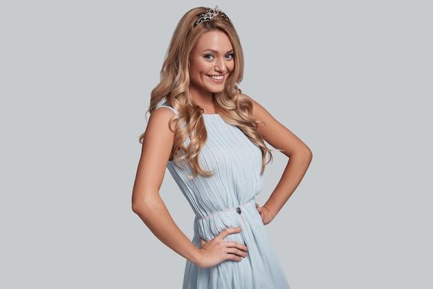 Po prostu szczęśliwy. atrakcyjna młoda kobieta trzymająca ręce na biodrach i patrząca na kamerę z uśmiechem, stojąc na szarym tle