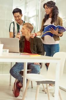 Po prostu to zrób. urocza brunetka trzyma książkę w lewej ręce podczas rozmowy z kolegą z klasy
