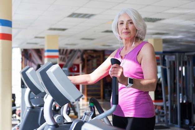 Po prostu wiem, czego chcę. pięknie zainspirowana starsza kobieta słuchająca muzyki i ćwicząca na rowerze stacjonarnym podczas spędzania czasu na siłowni.