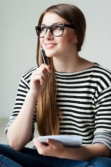 Po prostu zainspirowany. rozważna młoda kobieta w pasiastym ubraniu, trzymająca notatnik i dotykająca podbródka długopisem, siedząc na drewnianej podłodze