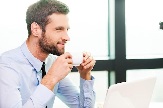 Po prostu zainspirowany. widok z boku myślący młody człowiek w koszuli i krawacie, trzymając filiżankę kawy i odwracając wzrok, siedząc w swoim miejscu pracy