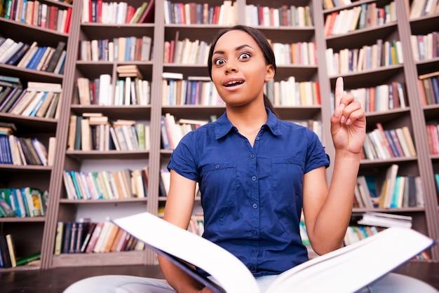 Po prostu zainspirowany. zaskoczona afrykańska studentka trzymająca książkę i wskazująca w górę, siedząca na podłodze w bibliotece