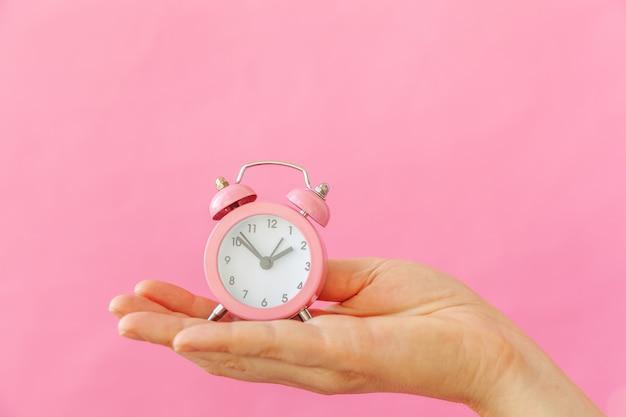 Po prostu zaprojektuj kobiecą rękę trzymającą dzwonek podwójnego budzika na białym tle na różowy pastelowy kolorowy modny
