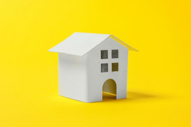 Po prostu zaprojektuj z miniaturowym białym domkiem z zabawkami na białym tle