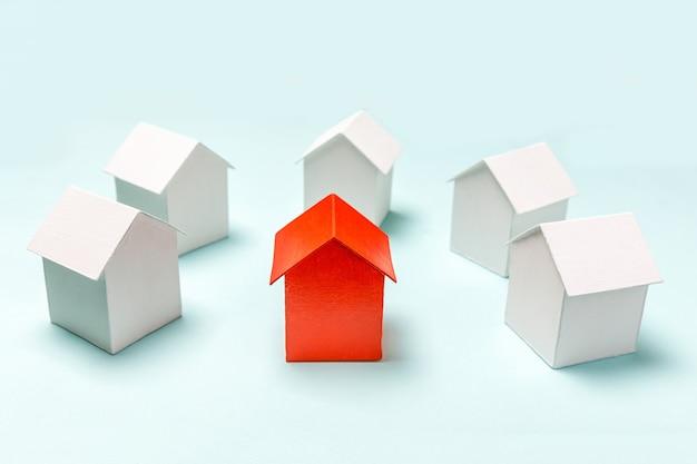 Po prostu zaprojektuj z miniaturowym czerwonym zabawkowym modelem domu wśród białych domów na pastelowym b...