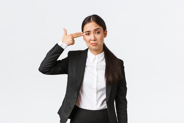 Po prostu zastrzel mnie proszę. zaniepokojona i znużona azjatycka sprzedawczyni nienawidzi swojej pracy, stojąc w garniturze, strzelając do siebie gestem pistoletu, jako uczucie wyczerpania, stojąc na białym tle