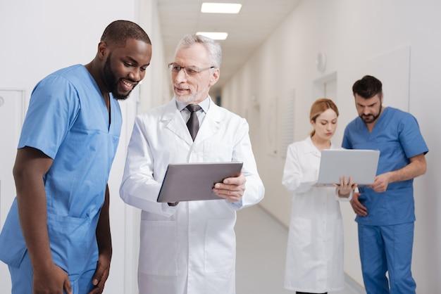 Po prostu zobacz różnicę. radosny, wykwalifikowany pediatra w podeszłym wieku, cieszący się pracą w szpitalu i pracy z tabletem, podczas gdy inni koledzy korzystają z laptopa w tle