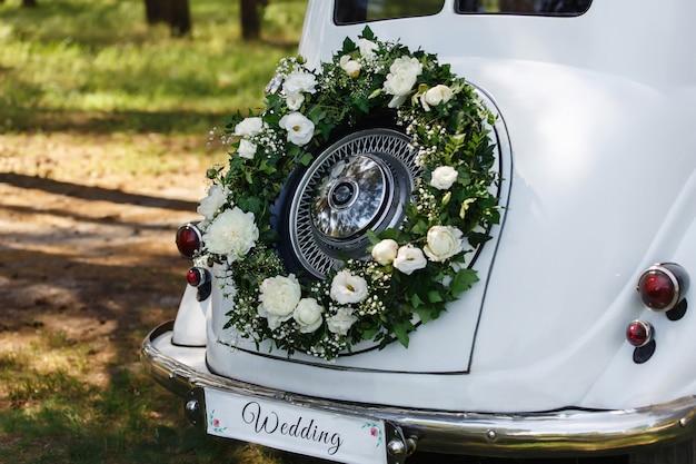 """Po prostu żonaty samochód z napisem """"ślub"""" i wieniec ze świeżych kwiatów"""